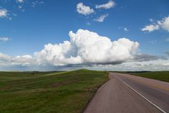 Road with Prairie and Storm. A dynamic view of a spring green prairie next to the road through Wind Cave National Park with ominous storm clouds in the distant stock photography