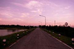 Road and purple sky in evening time Stock Images