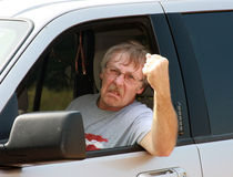 Road rage. Angry driver showing road rage by shaking his fist Stock Photos