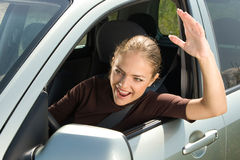 Road rage driver. Young woman driver yelling out car window Stock Image