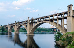 Road and rail split-level bridge over the river. On a background of blue sky in the city Royalty Free Stock Photos