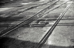 Road railtracks shadows. A black and white image of long shadows cast across disused rails in an industrial roadway stock photos