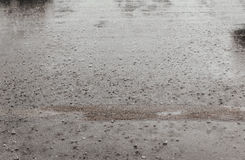 Road rain water drops background with blue sky reflection and circles on dark asphalt. forecast. Stock Images