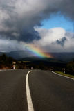 Road and Rainbow. Rainbow in a cloudy sky over a northland road Stock Images