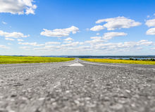 The road receding into the distance. The road goes into the distance through the field on a background of a beautiful summer landscape royalty free stock photos