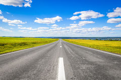 The road receding into the distance. The road goes into the distance through the field on a background of a beautiful summer landscape royalty free stock images