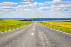 The road receding into the distance. The road goes into the distance through the field on a background of a beautiful summer landscape stock photos