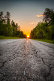 The road receding into the distance. The road through the woods, disappearing into the distance on the background of sunset royalty free stock photos