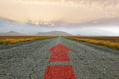 The road and the red arrow. The road at sunset with a red arrow Stock Photo
