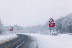 Road with Reduce speed now sign during snow fall Royalty Free Stock Photo