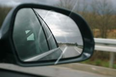 Road reflecting in wing mirror. Close up of highway reflecting in automobile wing mirror Stock Photos