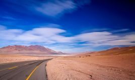 Road through the remote mountain plain. Road leading to the big salar near the famous Valle the la Luna near San Pedro de Atacama in Chile Stock Photos