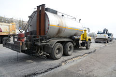 Road repair with a big tar machine filling seams. Machines for road repair. Stock Images