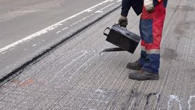 Road repair. Work details, workers pour resin road surface to cover the asphalt. Men in specialized clothing repair asphalt in the city. Preparation of asphalt stock video