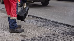 Road repair. Work details, workers pour resin road surface to cover the asphalt. Men in specialized clothing repair asphalt in the city. Preparation of asphalt stock video footage