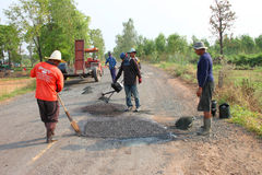 Road repairing. NACHAUK, MAHASARAKHAM, THAILAND - MARCH 19 : The unidentified workers are repairing local road on March 19, 2012 at Samrong - Porpan Way, Nachauk Royalty Free Stock Image
