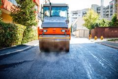 Road repairing in urban modern city with heavy vibration roller Royalty Free Stock Photos