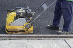 Road repairing with vibrating compactor plate royalty free stock images