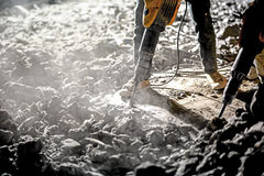 Road repairing works with jackhammer. At night Stock Photos
