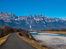 A road on the Rhein damn with mountains in the background. The road is leading along the Rhein and there are mountains and sandbanks in the photo Stock Photos