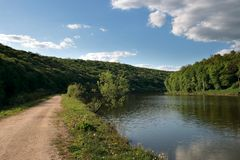 Road and river. Rural road along the river (Ukraine, Forest reserve Medobory Stock Photography