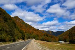 The road and the river on the background of yellow-green mountains and blue sky royalty free stock photos