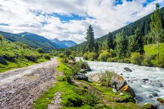 Road and river in Karakol national park, Kyrgyzstan Royalty Free Stock Image
