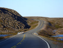 Road in rocky badlands. A road in a wasteland. Lonely cyclist Stock Photo