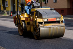 Road roller. With construction worker on bitumen road Stock Photos