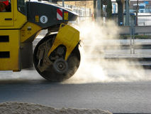 Road roller. A yellow road roller in a construction area. The hot asphalt is steaming royalty free stock photo