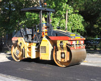 Road roller on asphalt. Road roller in action on urban street Royalty Free Stock Photo