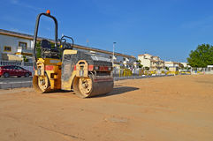 Road Roller. A road roller being used to flatten a sandy surface royalty free stock photography