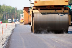 Road roller compacting asphalt pavement Stock Photos