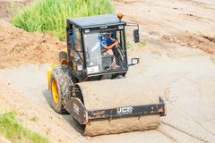 Road roller compressing sand to highway Stock Photography