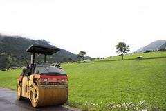 Road Roller machinery works outdoors at construction site. At grass field near Burgusio or Burgeis village at Malles Venosta, in val Venosta, in Trentino-Alto Stock Photo