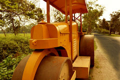 Road roller. A yellow road roller resting besides road. Photo taken in the month of April, 2016 Stock Photo