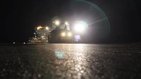 Road rollers leveling fresh asphalt pavement by night stock video