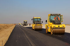 Road rollers leveling fresh asphalt pavement on a runway as part of the Danube Delta international airport expansion plan Royalty Free Stock Photo