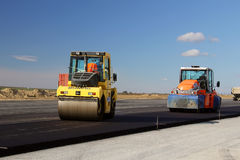 Road rollers leveling fresh asphalt pavement on a runway as part of the Danube Delta international airport expansion plan Stock Photos