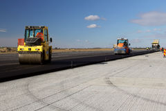 Road rollers leveling fresh asphalt pavement on a runway as part of the Danube Delta international airport expansion plan royalty free stock photography