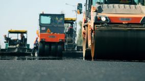 Road rollers work on a road during paving.