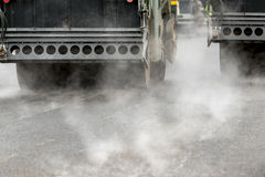 Road rolling machines working with steam on the asphalt Royalty Free Stock Photography