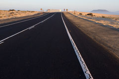 Road rough texture. Black asphalt way with white line in the middle. Sunrise, Spain, Fuerteventura Stock Images