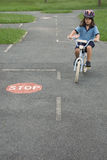Road rules training. A child rides her bicycle on a road rules training course, learning how to drive on the correct side of the road and stop at stop traffic Stock Image