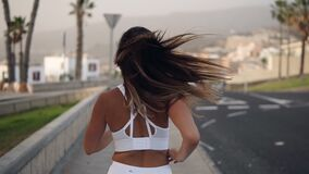 Road runner woman running by asphalt road , jogging along the palm grove in white sport clothes. Running woman outdoors