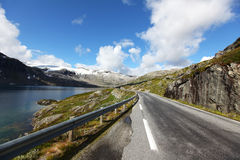 Road running through mountains with lake Royalty Free Stock Image
