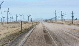 Road running Spinning wind turbines. A straight road splits a field of spinning wind turbines Royalty Free Stock Photography