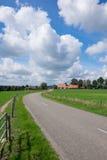 Road running thru landscape. Road running thru dutch landscape. Beautifull big clouds in the blue sky Royalty Free Stock Photos