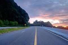 The road runs up the side of a mountain in the early morning. Hours Royalty Free Stock Photo