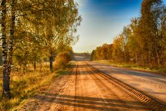 Road in rural district in autumn time Stock Photos